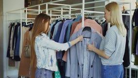Продавец помогает молодой женщине, приносит ее пальто и говорит о модели Клиент касается ему, сравнивающ сток-видео