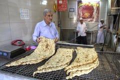 Продавец рассматривает свеже испеченный хлеб пита в иранское традиционном Стоковые Изображения RF