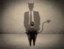 Продавец смотря на его собственную тень дьявола Стоковое Изображение RF
