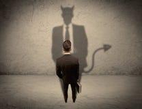 Продавец смотря на его собственную тень дьявола Стоковое Изображение
