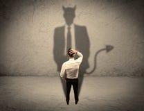 Продавец смотря на его собственную тень дьявола Стоковые Изображения