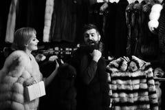 Продавец с бородой и женщина покупают меховое пальто стоковая фотография rf