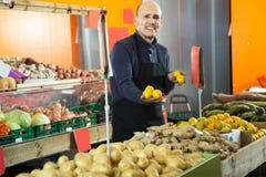 Продавец с лимоном в vegetable магазине Стоковое фото RF