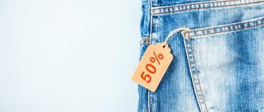Продажа, скидка, черная концепция пятницы с биркой, голубыми джинсами на светлой предпосылке знамена стоковые изображения rf