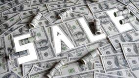 Продажа слова на предпосылке счетов 100-доллара, изоляте Стоковое Фото