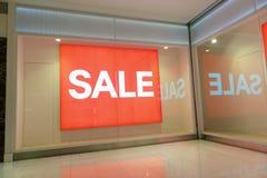 Продажа текста красного знака белая в дисплее магазина стоковое изображение