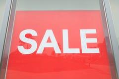 Продажа текста красного знака белая в дисплее магазина стоковая фотография rf