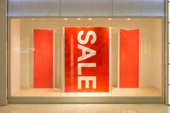 Продажа текста красного знака белая в дисплее магазина стоковые фотографии rf