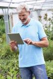 Продажи ассистентские в садовом центре с таблеткой цифров стоковое фото rf