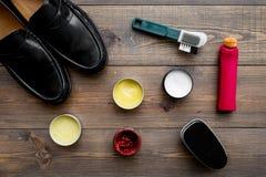 Продукты заботы ботинка Кожаные ботинки людей, заполированность ботинка, щетки, воск на темном деревянном взгляд сверху предпосыл Стоковое фото RF
