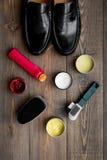 Продукты заботы ботинка Кожаные ботинки людей, заполированность ботинка, щетки, воск на темном деревянном взгляд сверху предпосыл Стоковые Изображения RF