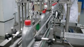 Продукция автотракторных масел, автоматическая линия транспортера для закрывает крышки на пластиковых бутылках на фабрике сток-видео