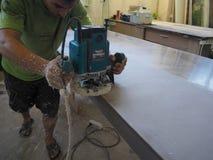 Продукция акриловых worktops на фабрике мебели Работник производит акриловые countertops на фабрике Заполированности работника Стоковые Изображения RF