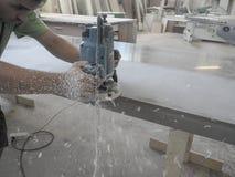 Продукция акриловых worktops на фабрике мебели Работник производит акриловые countertops на фабрике Заполированности работника Стоковая Фотография
