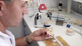 Продукция зубных имплантатов, профессионал делает керамические зубы в специальных приборах и отбеливателях с порошком на работе сток-видео