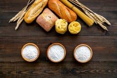 Продукция пекарни, делающ хлеб и макаронные изделия Свежий хлеб и сырцовые макаронные изделия около муки в ушах шара и пшеницы на стоковые фото