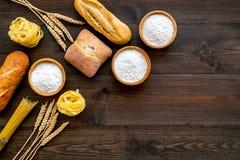 Продукция пекарни, делающ хлеб и макаронные изделия Свежий хлеб и сырцовые макаронные изделия около муки в ушах шара и пшеницы на стоковое фото