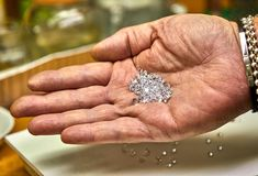 Продукция ювелирных изделий Монтер держит диаманты на ладони перед отладкой стоковая фотография