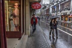 Проезжие пропускают вдоль влажного pavementwalked прошлого магазина на улице города Стоковая Фотография