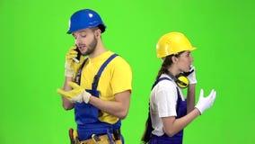 Проектирует парня при девушка говоря на различных телефонах зеленый экран движение медленное акции видеоматериалы