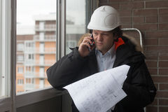Проектируйте положение на предпосылке нового жилого дома построенная дом Инженер в шлеме с бумагами внутри Стоковые Изображения