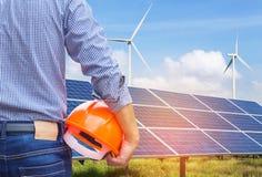 Проектируйте стойку держа шлем безопасности желтый при фотоэлементы и ветротурбины производя электричество в гибридной системе эл стоковые изображения rf