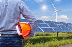 Проектируйте стойку держа шлем безопасности желтый при фотоэлементы и ветротурбины производя электричество в электростанции Стоковые Фото