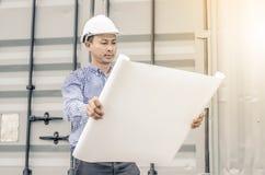 Проектируйте человека при шлем смотря бумажные планы на строительной площадке Стоковые Фото