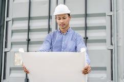 Проектируйте человека при шлем смотря бумажные планы на строительной площадке Стоковые Фотографии RF