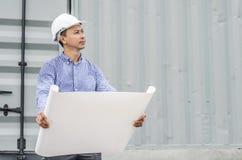 Проектируйте человека при шлем смотря бумажные планы на строительной площадке Стоковое фото RF