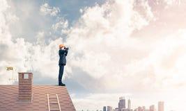 Проектируйте человека стоя на крыше и смотря в биноклях Смешанный m Стоковые Изображения