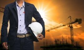 Проектируйте человека стоя с белым шлемом безопасности против красивого Стоковая Фотография