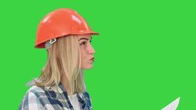 Проект довольно молодой женщины инженера рассматривая планирует анализировать дизайн проекта на зеленом экране, ключ схемы Chroma сток-видео