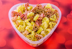 Прозрачная ваза формы сердца (шар) заполненная с покрашенными (красный цвет, желтеет апельсин) макаронными изделиями формы сердца Стоковое Изображение