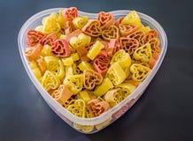 Прозрачная ваза формы сердца (шар) заполненная с покрашенными (красный цвет, желтеет апельсин) макаронными изделиями формы сердца Стоковое фото RF