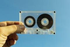 Прозрачная магнитофонная кассета в руке стоковая фотография rf