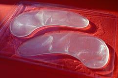 Прозрачные белые косметические заплаты глаза в прозрачной коробке на красной предпосылке, без стороны, на солнечном свете стоковое изображение
