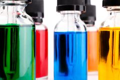 Прозрачные стеклянные заполненные бутылки покрасили жидкость с капельницей Стоковая Фотография