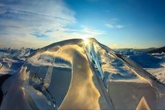 Прозрачный голубой лед Toros Байкала сияющий через великолепный заход солнца стоковые фото