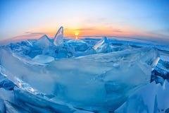 Прозрачный голубой лед Toros Байкала сияющий через великолепный заход солнца стоковые изображения rf