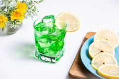 Прозрачный зеленый напиток в стекле с куском кубов лимона и льда Куски лимона на голубой плите стоковое изображение