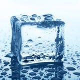 Прозрачный куб льда на синем стекле с падением воды Стоковое Изображение