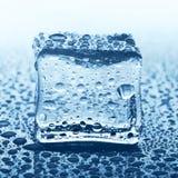 Прозрачный куб льда на синем стекле с падением воды Стоковая Фотография