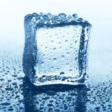 Прозрачный куб льда на синем стекле с падением воды Стоковое фото RF
