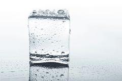 Прозрачный куб льда с отражением на белизне Стоковое Фото