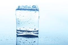 Прозрачный куб льда с отражением изолированный на белизне Стоковые Изображения