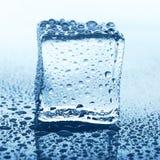 Прозрачный куб льда с отражением на синем стекле с водой падает Стоковые Изображения RF
