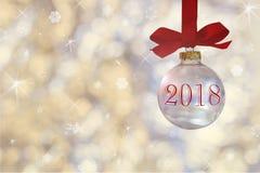 Прозрачный пустой шарик рождества Безделушка рождества, виды на красной ленте на предпосылке defocused серебряных светов Стоковое Изображение