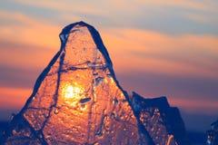 Прозрачный фиолетовый лед Байкала торошения сияющий через великолепный заход солнца стоковое фото