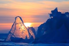 Прозрачный фиолетовый лед Байкала торошения сияющий через великолепный заход солнца стоковые фото